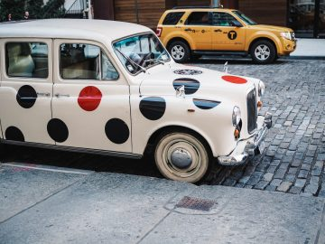 An old-timey car covered in red and black vinyl polka dots